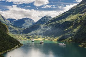 two big ships in famous Geirangerfjord in Norway between steep mountains.